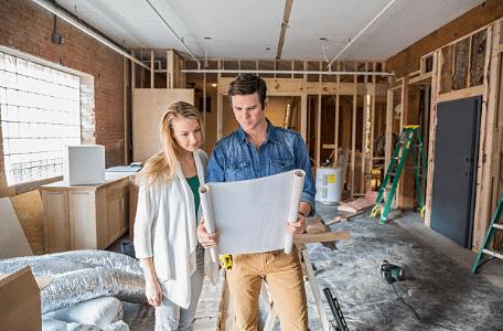 deux personnes regardant des plans dans une maison en construction