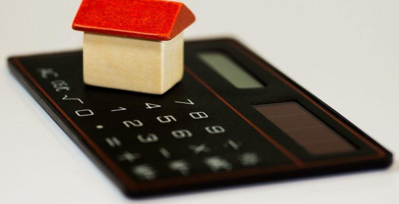 miniature de maison posée sur un calculatrice