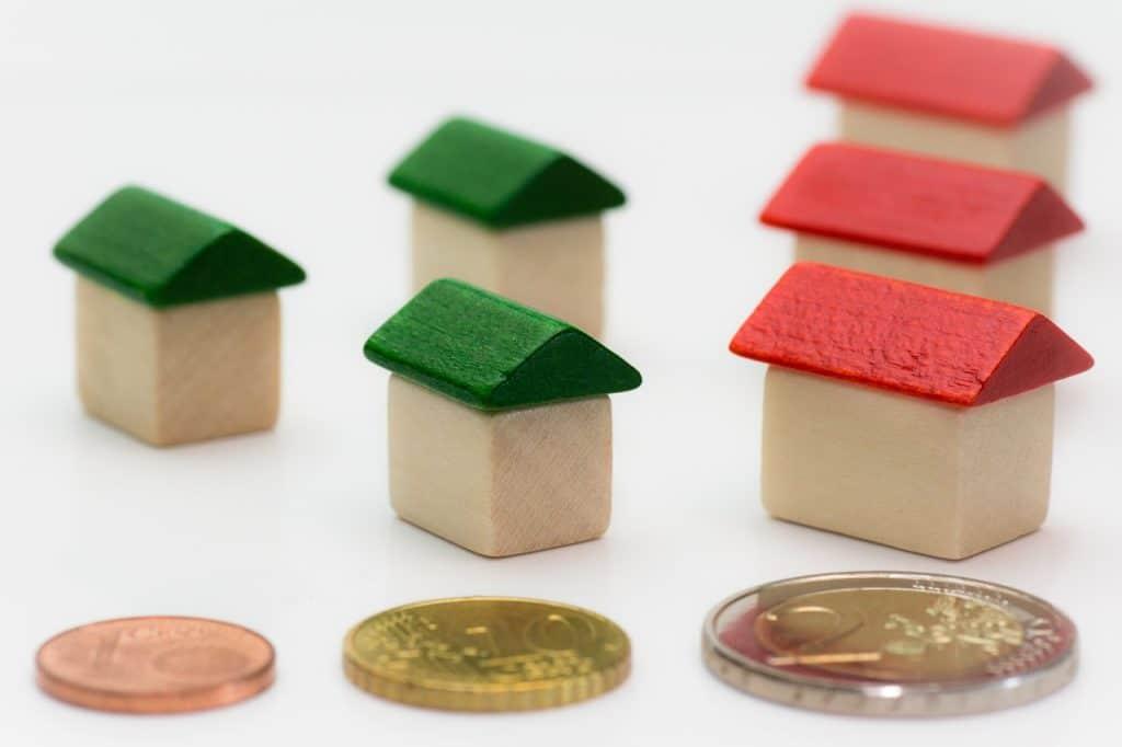 pièces de monnaie posées devant des maisons miniatures